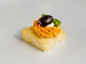 Light Cream Cheese with Tomato Tapenade with Asparagus and Olive Garnish on croute